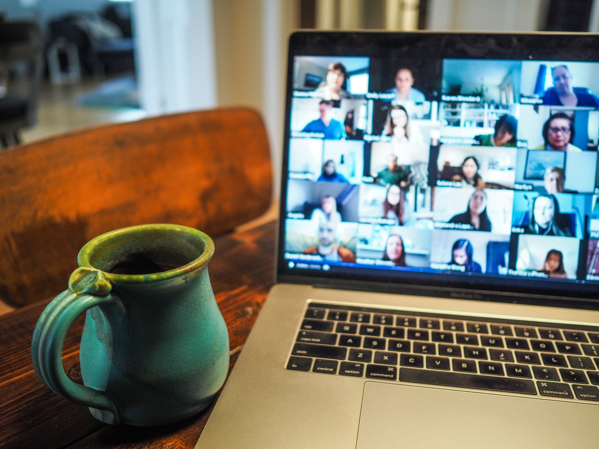A jug next to a laptop showing a Zoom meeting.