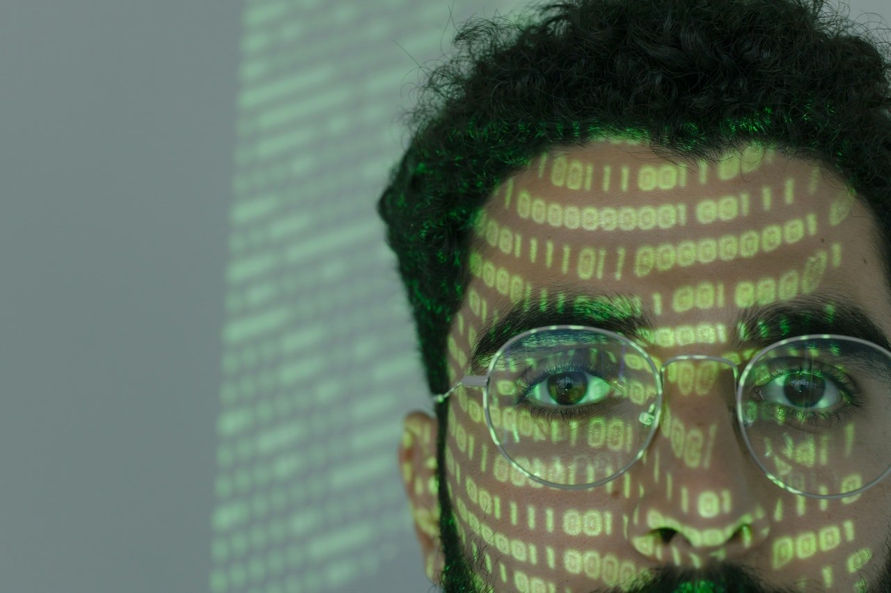man with glasses looking at a screen with 0s and 1s