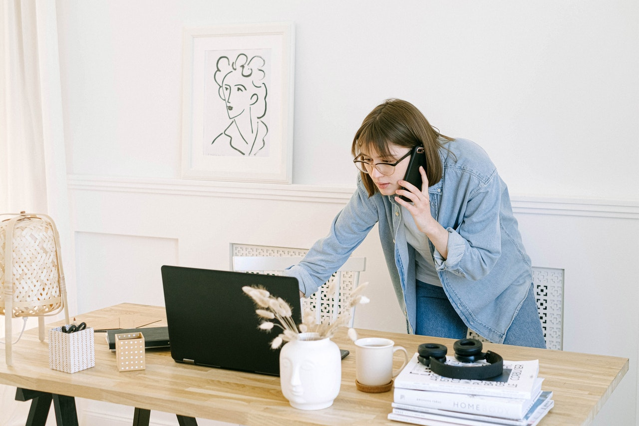 woman on phone, pointing at her laptop